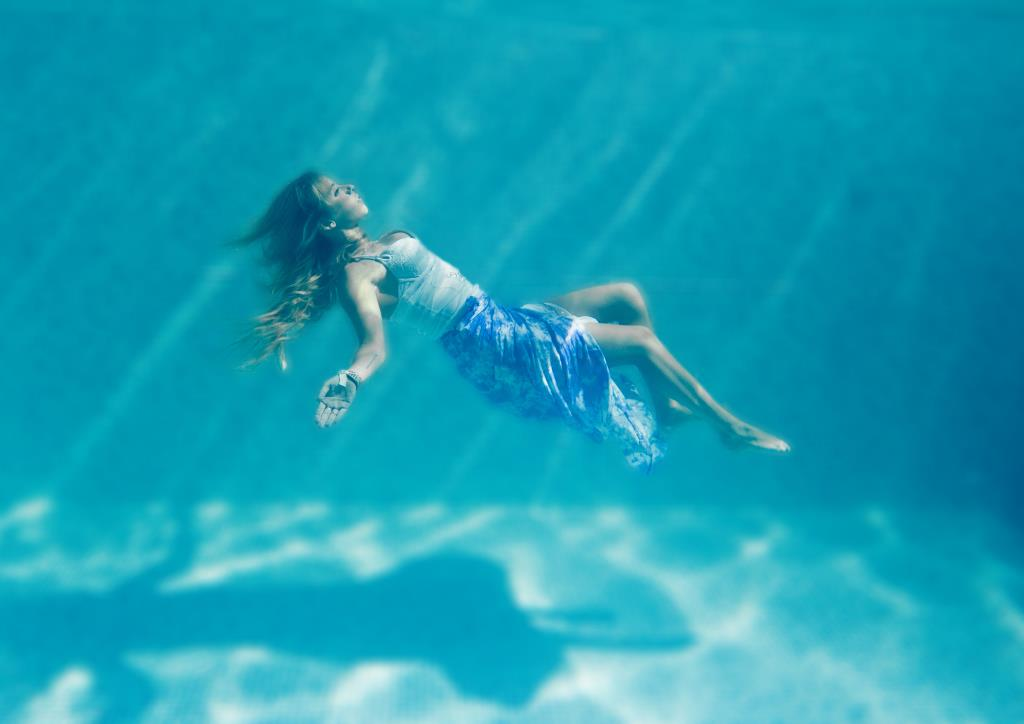 Under water swimming pool portrait blonde teenage girl