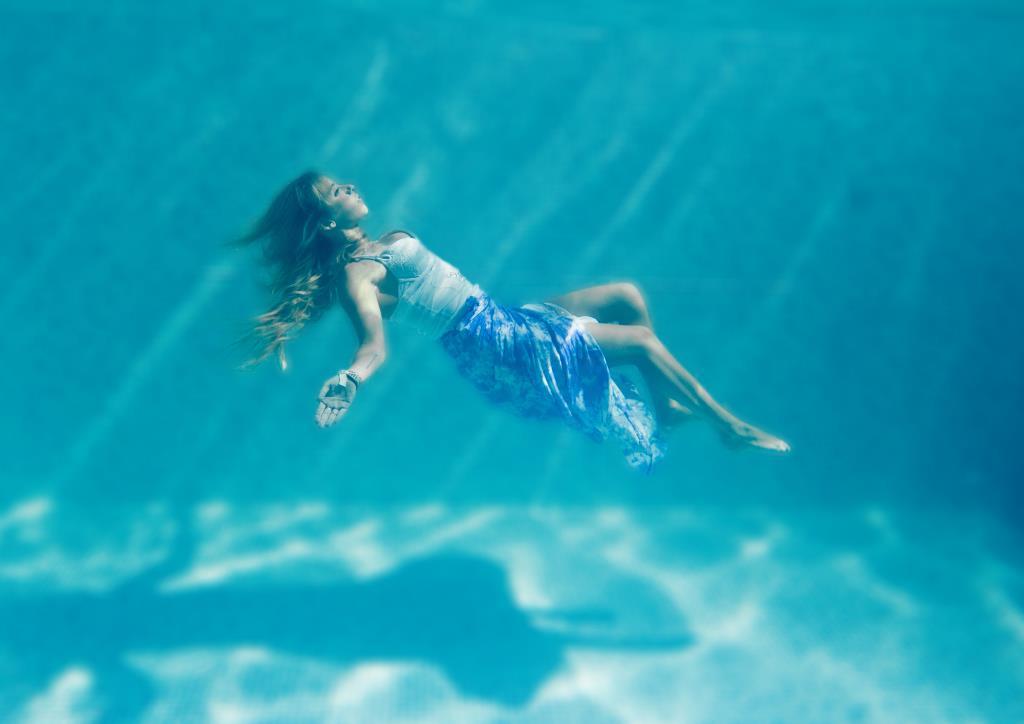 Under water swimming pool portrait blonde teenage girl
