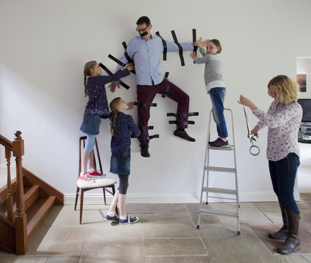 Fun family photography taping dad to the wall